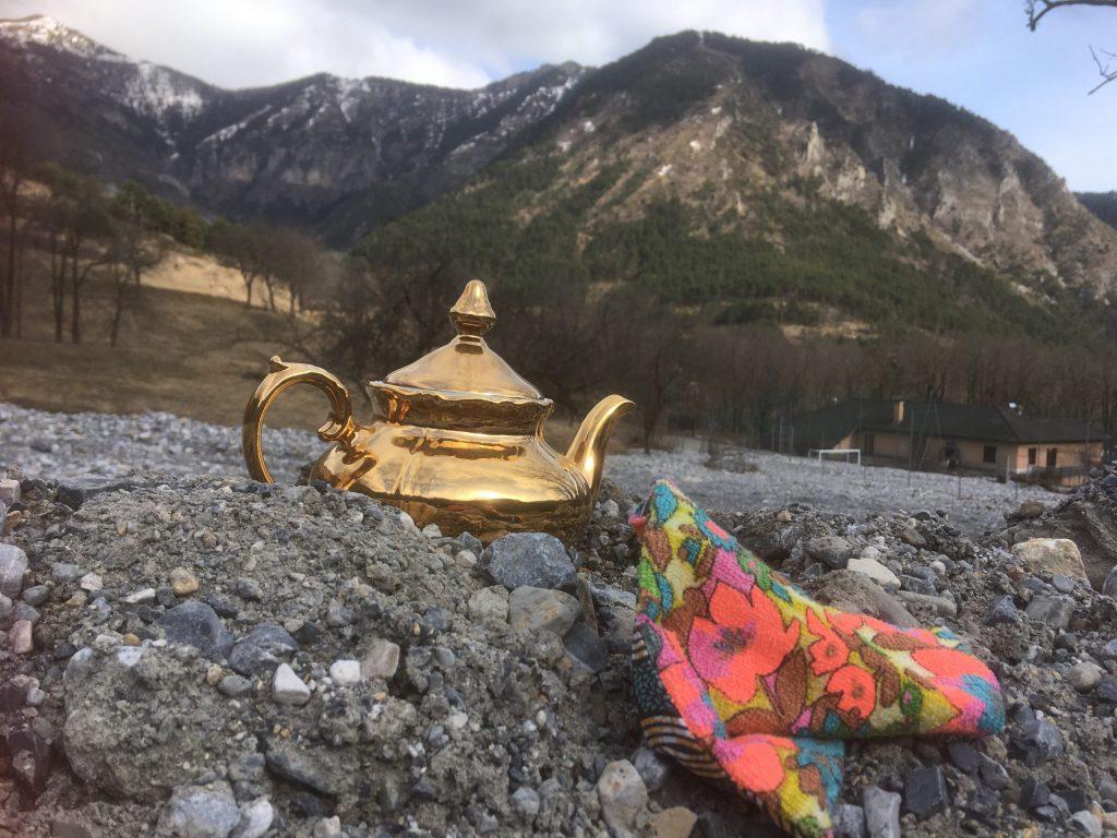 coussin caillou coloré à côté d'un vieille théière posés dans la vallée de la roya